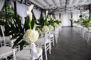 Gorgeous white flowers and stately palms create a dramatic setting for a wedding.